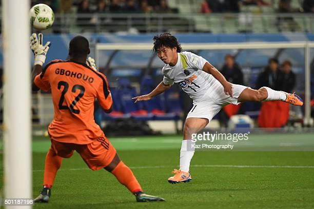 Hisato Sato of Sanfrecce Hiroshima beats Sylvain Gbohouo of TP Mazembe but misses the frame at Osaka Nagai Stadium on December 13 2015 in Osaka Japan