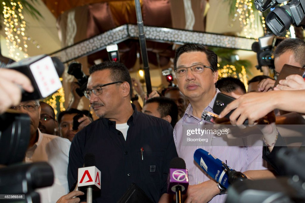 Hishammuddin Hussein, Malaysia's defence minister, left, and Liow Tiong Lai, Malaysia's transport minister, surrounded by media, enter the Sama Sama Hotel in Sepang, Malaysia, on Saturday, July 19, 2014. Hishammuddin said the investigation team should be allowed to access the crash site. Photographer: Brent Lewin/Bloomberg via Getty Images