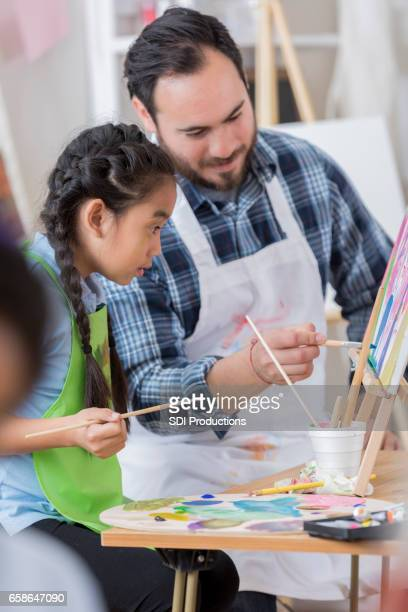 Hispanic art teacher works with young student