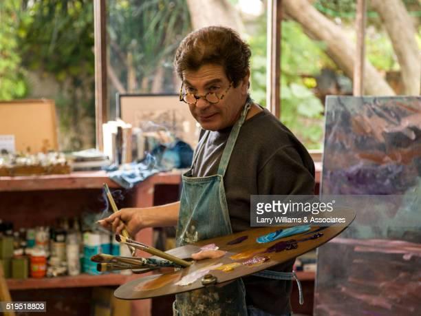 Hispanic artist holding palette in studio