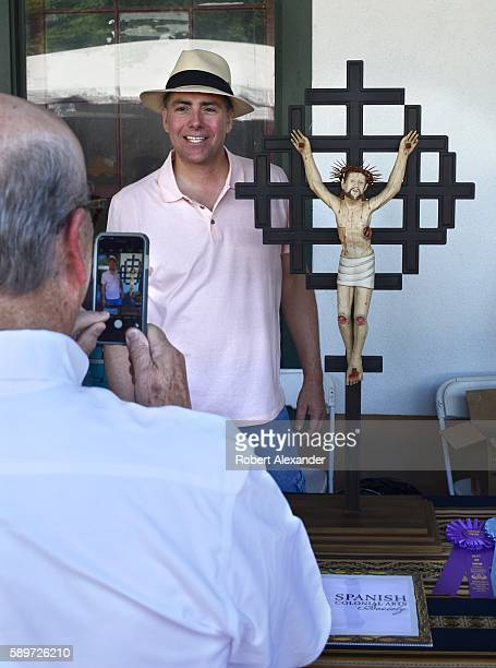 Hispanic artist Joseph Ascension Lopez poses for a photograph with his painted wooden bulto at the Spanish Market on July 30 2016 in Santa Fe New...