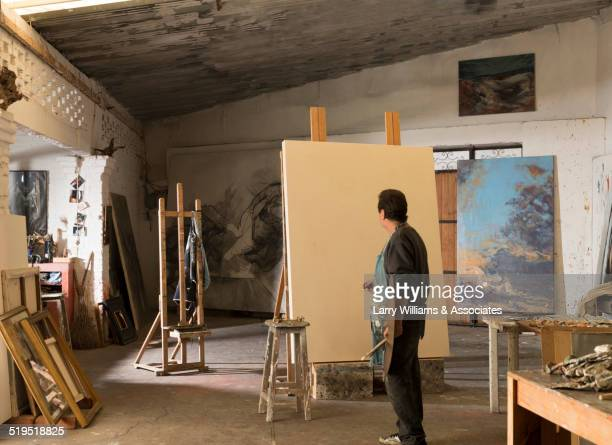 Hispanic artist painting in studio