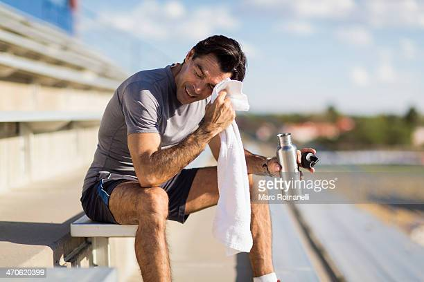 Hispanic athlete resting on bleachers
