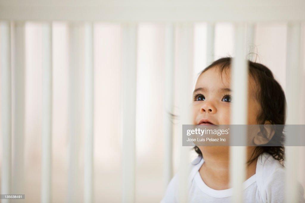 Hispanic baby girl sitting in crib : Stock Photo