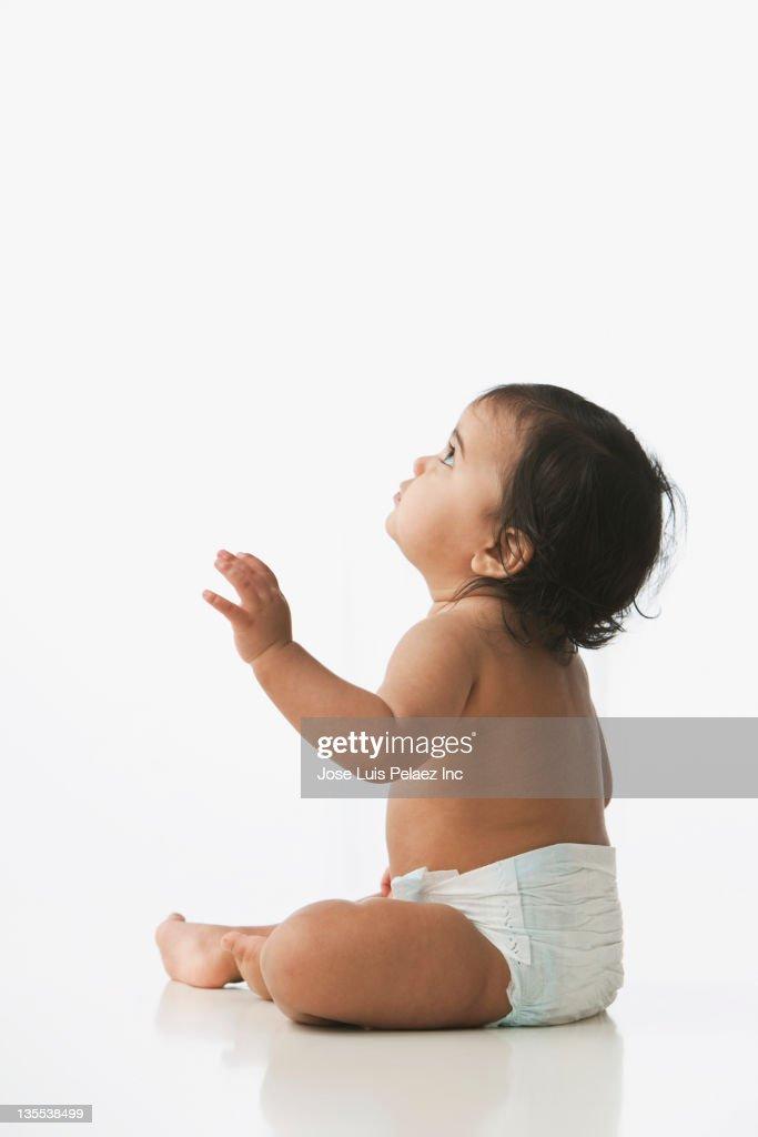 Hispanic baby girl sitting on floor : Stock Photo