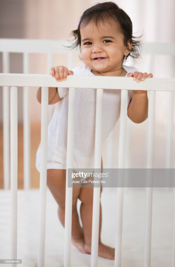 Hispanic baby girl standing in crib : Stock Photo
