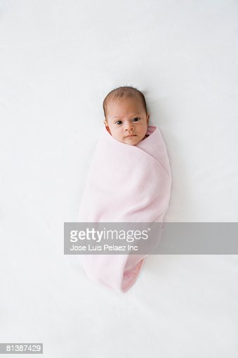 Hispanic baby wrapped in pink blanket
