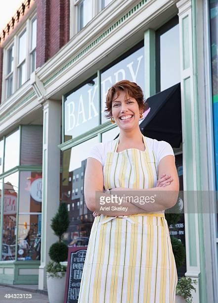 Hispanic baker smiling outside shop