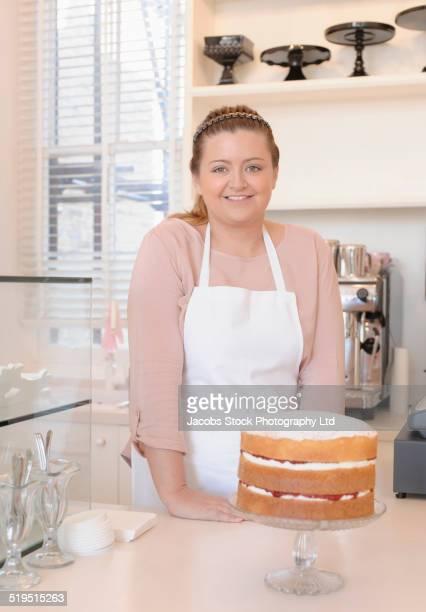 Hispanic baker smiling with cake in bakery