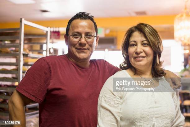 Hispanic bakers smiling in kitchen