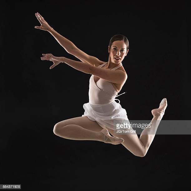 Hispanic ballet dancer leaping in mid-air