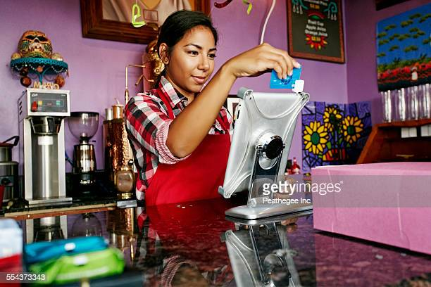 Hispanic barista using digital tablet register in coffee shop
