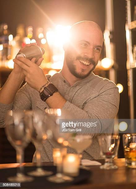 Hispanic bartender making drinks at bar