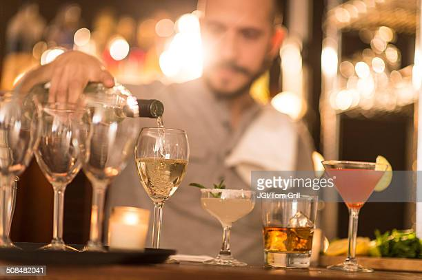 Hispanic bartender pouring drinks at bar