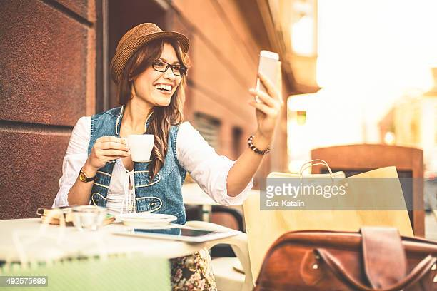 Hispanic beauty texting and enjoying a cup of coffee
