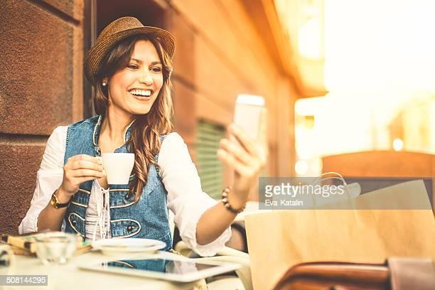Hispanic belleza enviando mensajes de texto y disfruta de una taza de café