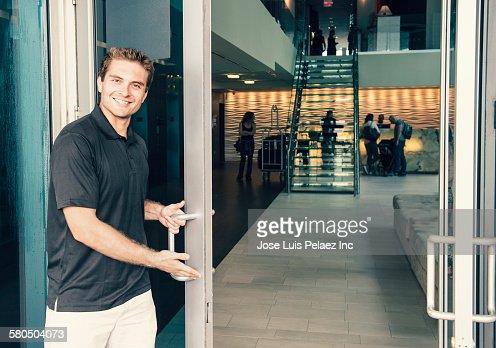 Hispanic bellboy opening hotel door