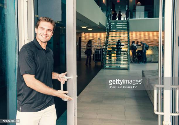 Hispanic bellboy opening hotel door