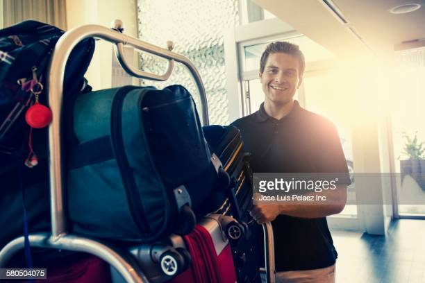 Hispanic bellboy pushing luggage cart in hotel