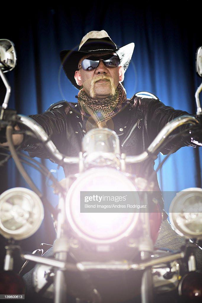 Hispanic biker sitting on motorcycle