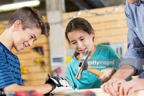 Hispanic boy and girl building something with father in workshop