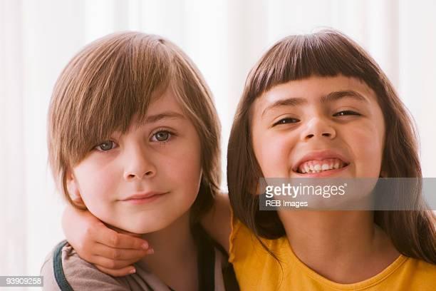 Hispanic boy and girl hugging
