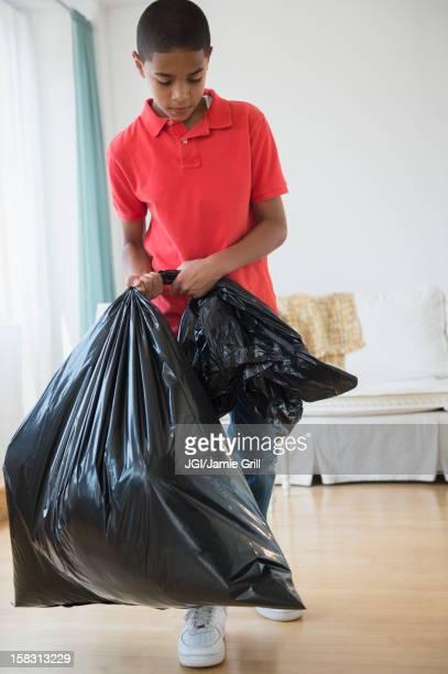 Hispanic boy carrying garbage bag