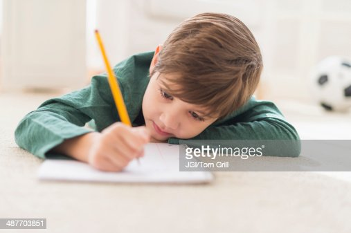 Hispanic boy doing homework on floor : Stock Photo