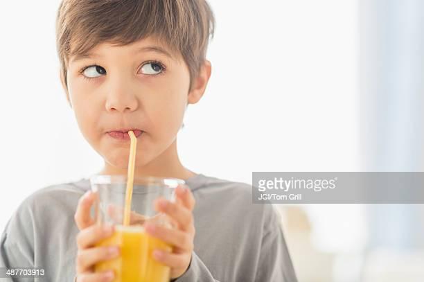 Hispanic boy drinking juice with straw