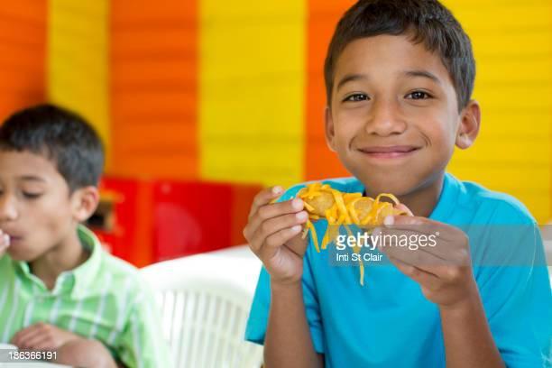 Hispanic boy eating in restaurant