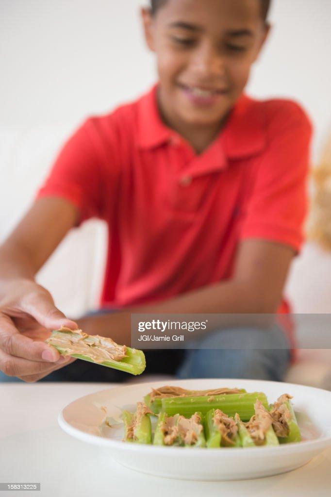 Hispanic boy eating peanut butter on celery : Stock Photo