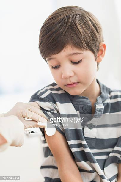 Hispanic boy getting a shot at doctor's office