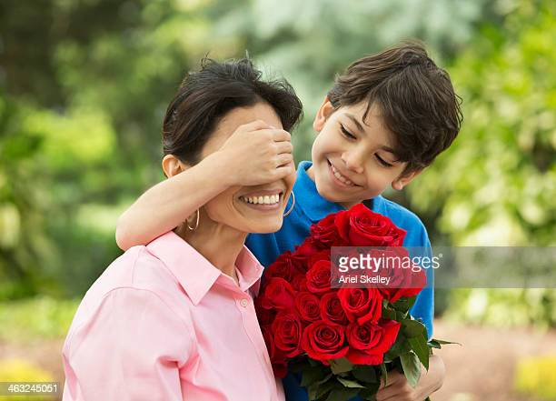 Hispanic boy giving mother bouquet of roses
