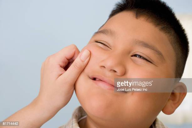 Hispanic boy having cheek pinched