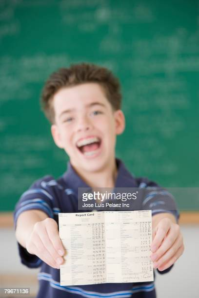 Hispanic boy holding report card
