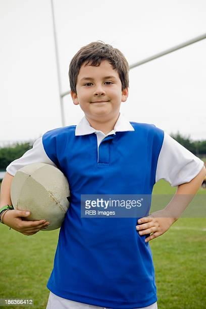 Hispanic boy holding rugby ball on field