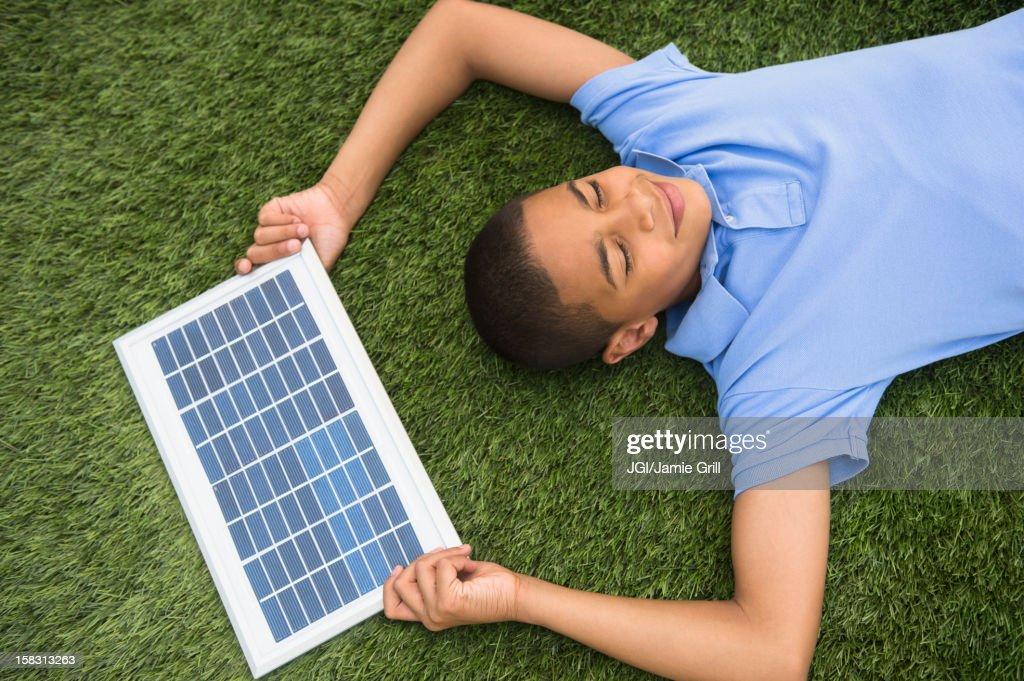 Hispanic boy holding solar panel : Stock Photo