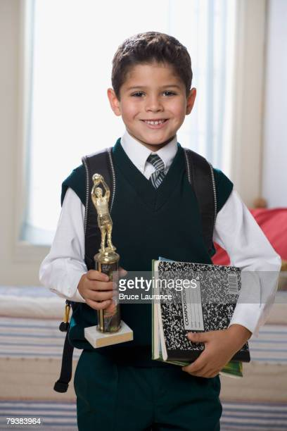 Hispanic boy holding trophy and school books