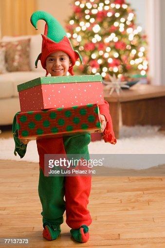 Hispanic boy in elf costume carrying gifts