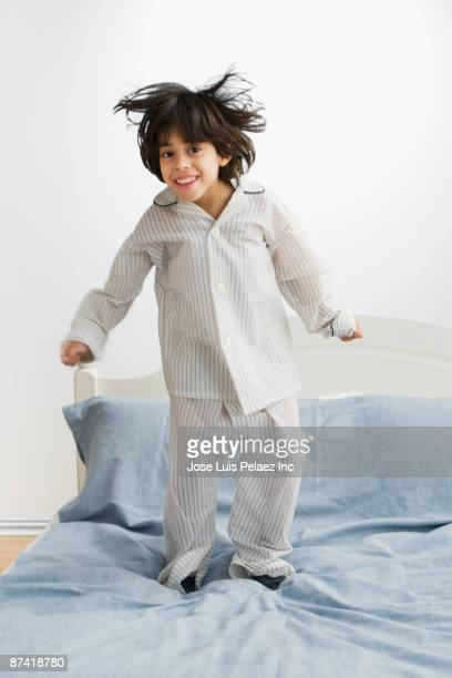 Hispanic boy in pajamas jumping on bed