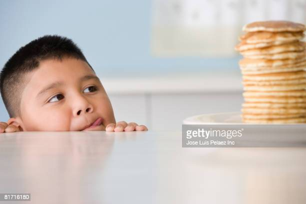 Hispanic boy licking lips at stack of pancakes