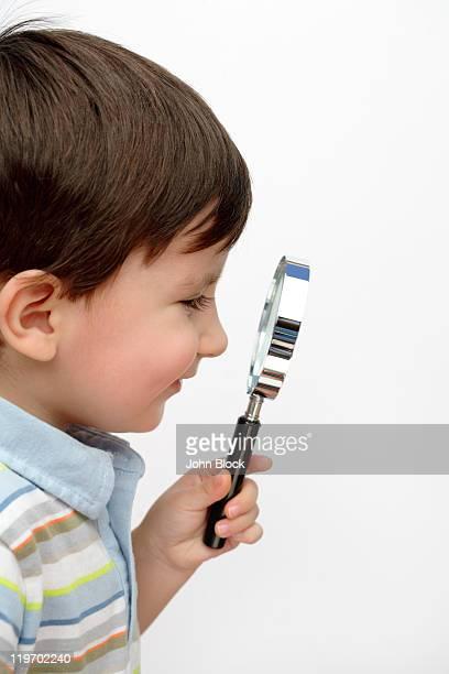 Hispanic boy looking through magnifying glass