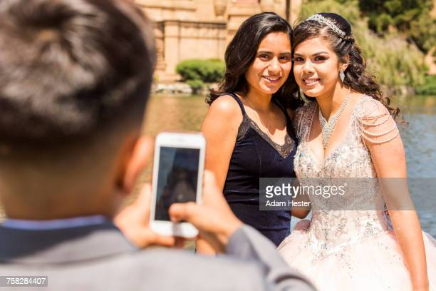 Hispanic boy photographing girls with cell phone