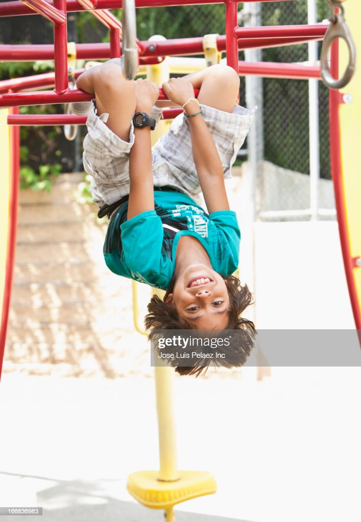 Hispanic boy playing on jungle gym at playground