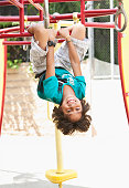 Hispanic boy playing on jungle gym at playground