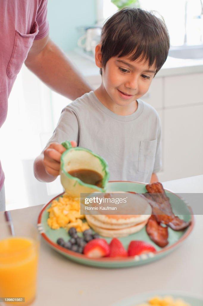 Hispanic boy pouring syrup on pancakes : Stock Photo