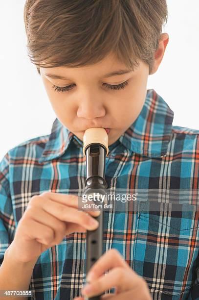 Hispanic boy practicing recorder