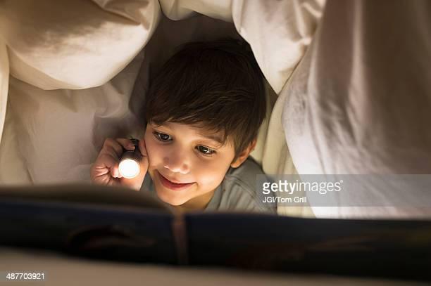 Hispanic boy reading under covers