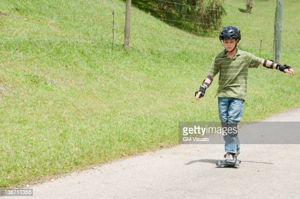 Hispanic boy riding skateboard on road