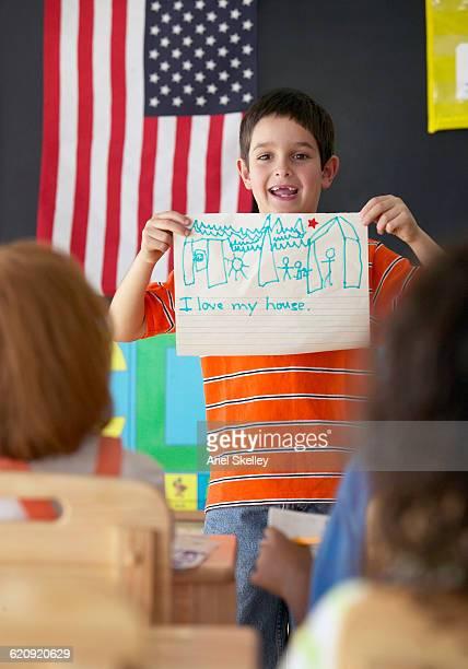 Hispanic boy showing drawing to class